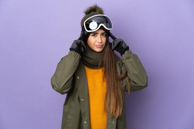 Женщина-лыжница в очках для сноуборда изолирована на фиолетовой стене с сомнениями и мышлением