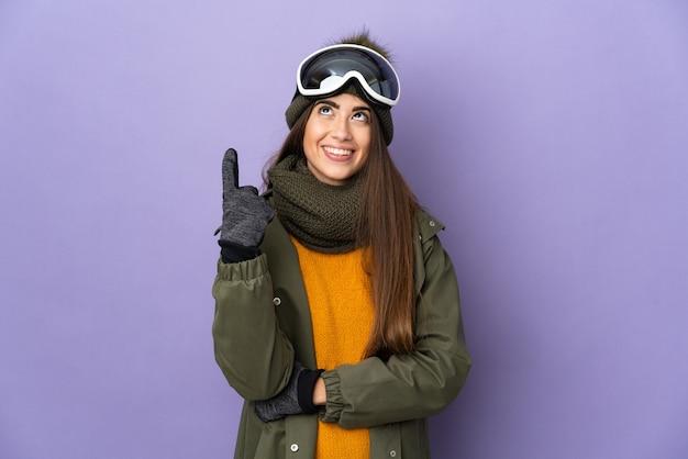 Женщина-лыжница в очках для сноуборда изолирована на фиолетовой стене, указывая на отличную идею