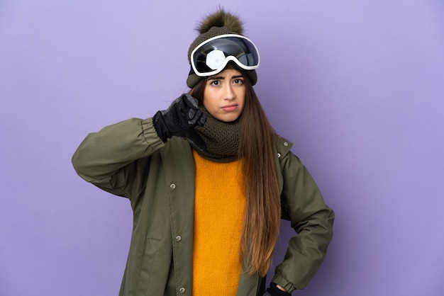 Женщина-лыжница в очках для сноуборда изолирована на фиолетовой стене, показывая большой палец вниз с отрицательным выражением лица