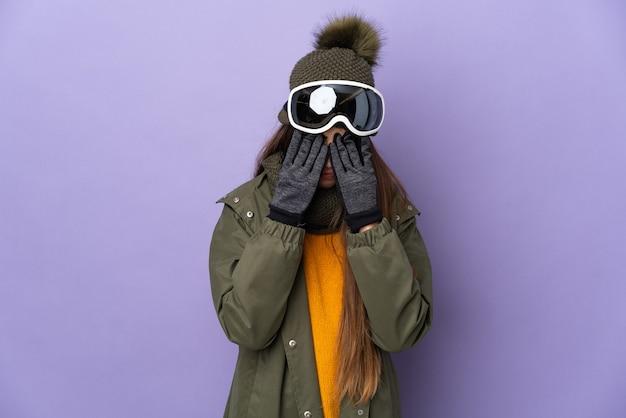 Женщина-лыжница в очках для сноуборда изолирована на фиолетовой стене с усталым и больным выражением лица