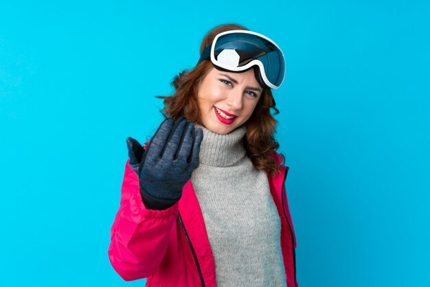 Skier woman with snowboarding glasses over isolated wall