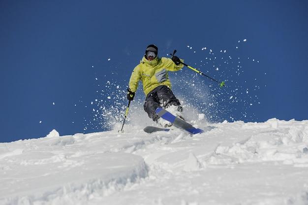 Skier in yellow sportswear riding down the mountain slope in georgia, gudauri