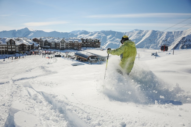 Skier in yellow sportswear riding down the slope in georgia, gudauri