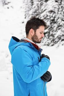 スキーヤーが雪山で彼のジャケットをジッパー