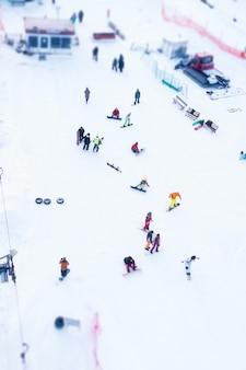 겨울 세로 샷의 눈 덮인 슬로프에서 스키어와 스노보더