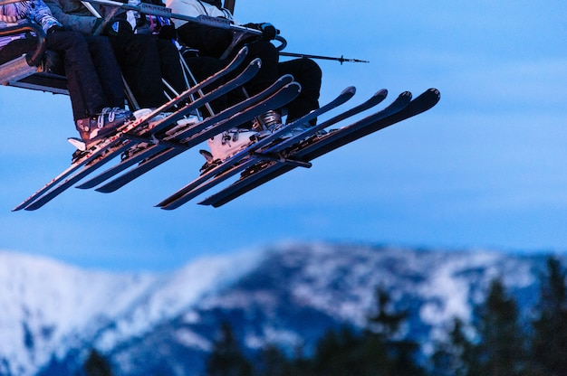 Skiers on chair lifts in the evening