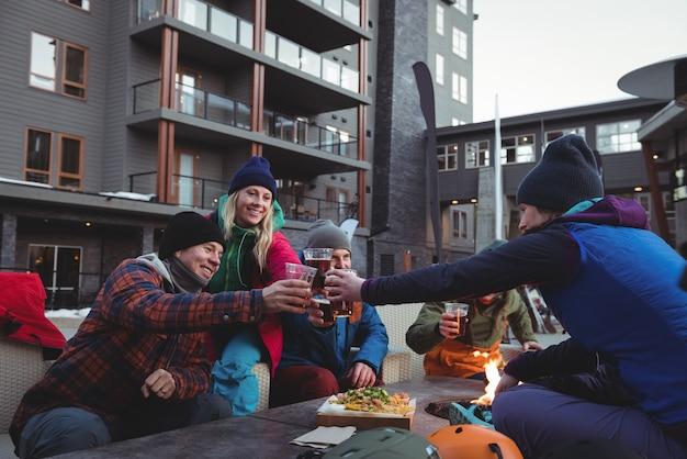 Amici di sciatori che tostano bicchieri di birra nella località sciistica