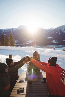 スキーリゾートでビールのグラスを乾杯するスキーヤーの友人