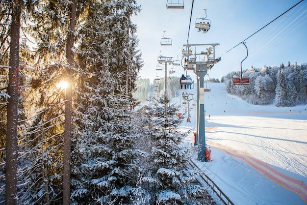 スキー場でスキーリフトに乗るスキーヤー