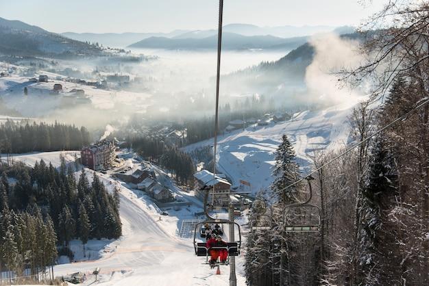スキーリゾートのスキーリフトに乗るスキーヤー