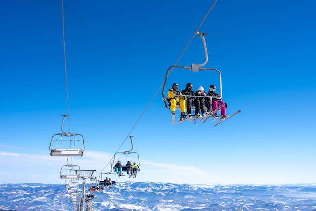 Skiers on a ski lift at a mountain resort with the sky and mountains in the background