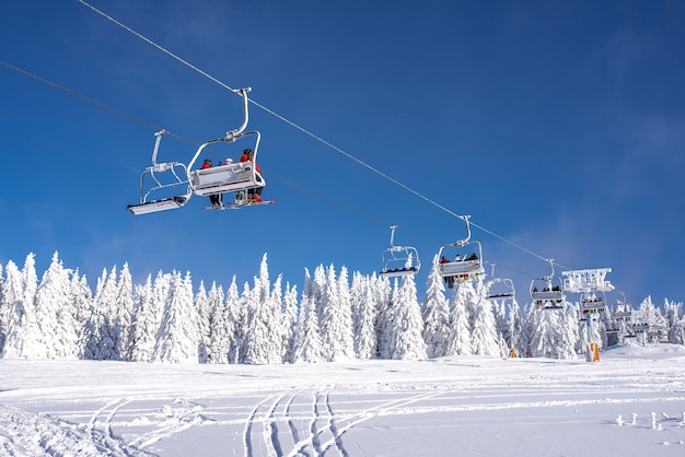 Skiers on a ski lift at a mountain resort with the sky and mountains