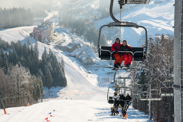 Skiers on the ski lift riding up at ski resort with background of snow-covered slopes, forests, hills