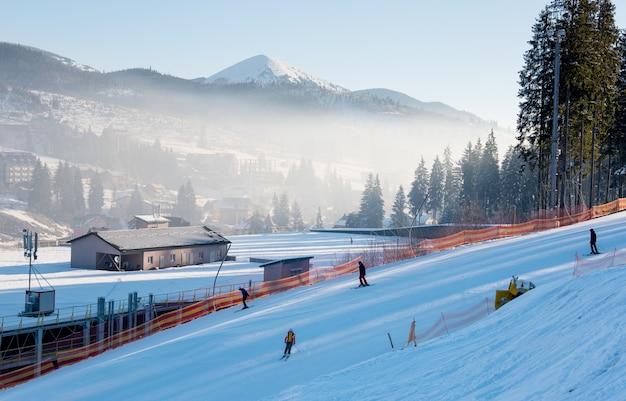 丘を下ってスキーをするスキーヤー