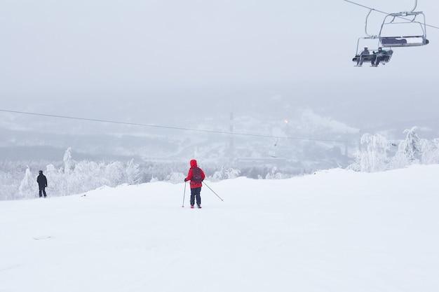 Лыжники спускаются на лыжах и поднимаются на кресельном подъемнике в холмистом зимнем пейзаже
