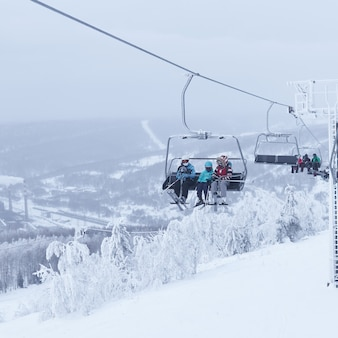 Лыжники на кресельном подъемнике в холмистом зимнем пейзаже