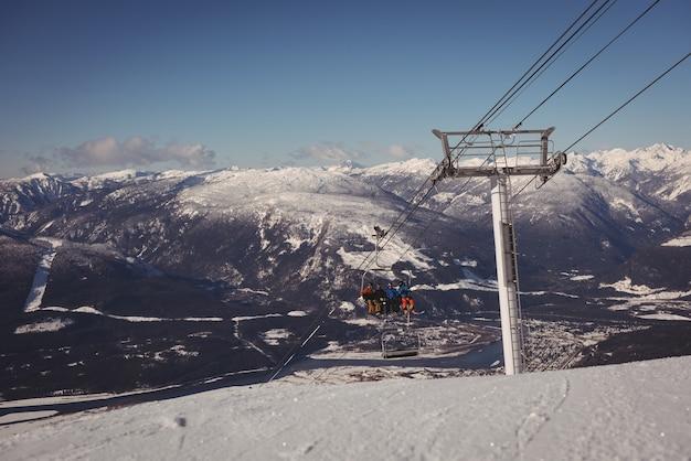 스키장에서 스키 리프트로 여행하는 스키어