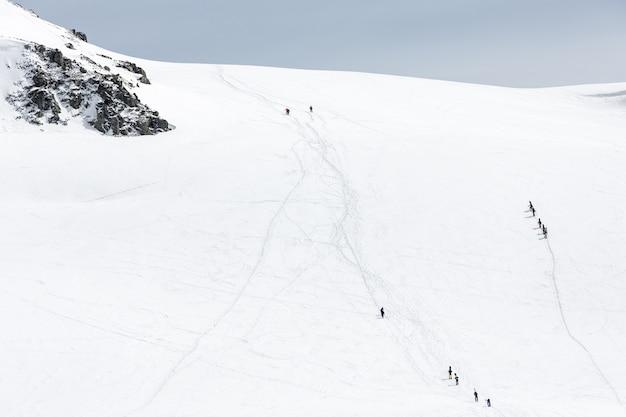 雪に覆われた山脈を歩くスキーヤー
