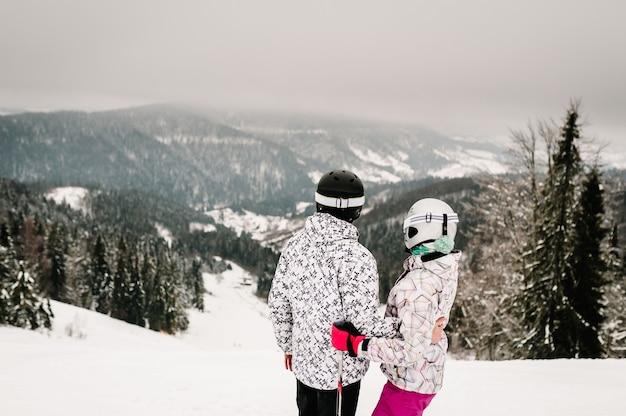 スキー。雪山でスキーをするカップル。カルパティア山脈の雪の上のスキーでスキーマスクの男性と女性。