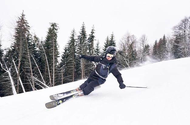 高山からスキーダウン。スキーヤーは、曲がって雪の上に落ちるときに不運な操縦をします。正面のモノクロビュー。