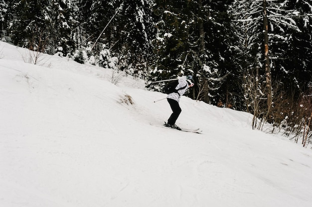 スキー。極端なウィンタースポーツ。ジャンプスキーヤー。フリーライドスキー。雪山でのスキーが上手です。カルパティア山脈の雪の上のスキーでスキーマスクの男。