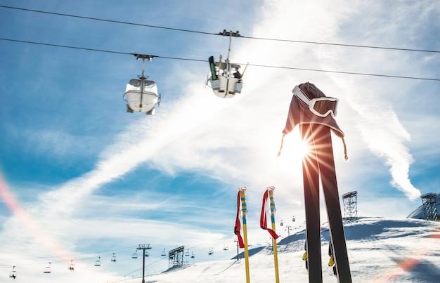 Лыжные очки и лыжные палки на курортном леднике с кресельным подъемником во французских альпах