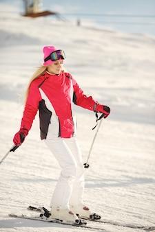 山でのスキー。スキーウェアの鮮やかな色。女の子はスキーに時間を費やしています。