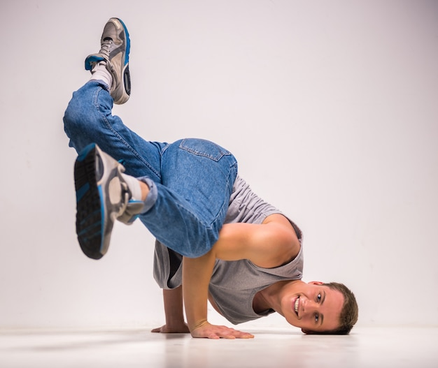 Skilful breakdancer posing on his hands at studio.