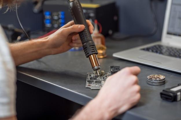 Мастерство, опыт. умелые мужские руки паяют микросхему на столе возле ноутбука в мастерской