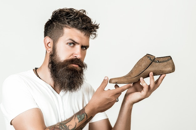 Skilled authentic shoemaker. modelling new shoes. handsome bearded shoemaker