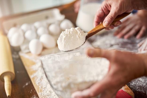 반죽을 만들기 위해 한 숟가락의 밀가루를 들고 있는 숙련된 제빵사