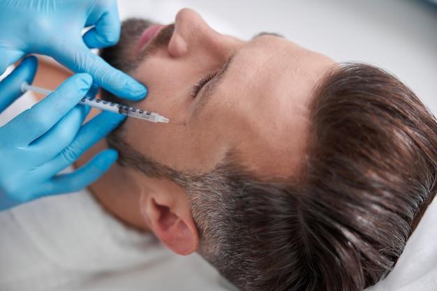Квалифицированный косметолог делает инъекцию наполнителя для гусиных лапок клиенту-мужчине среднего возраста