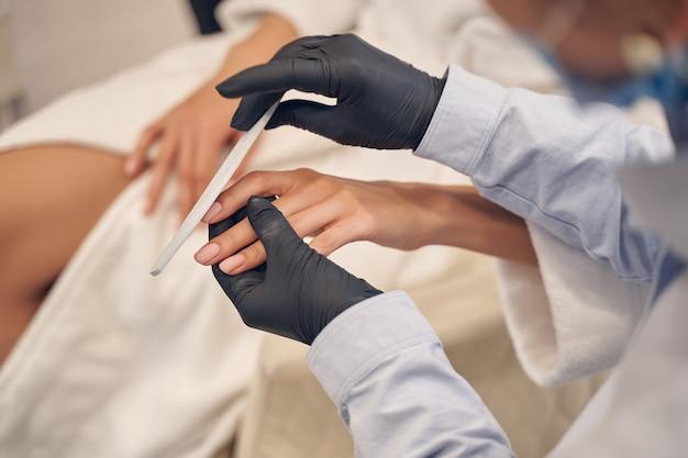 Опытный бьюти-мастер аккуратно подпиливает ногти клиенту в черных перчатках