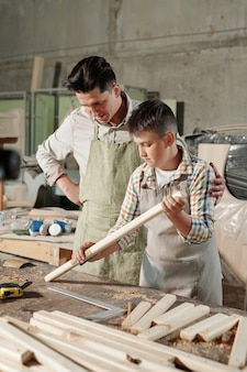 Skilled carpenter in apron supporting son while he learning to polish wood with sandpaper in workshop
