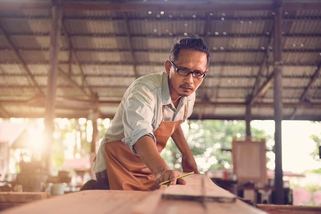 Опытный плотник, вырезающий кусок дерева в своей столярной мастерской, плотники, использующие циркулярную пилу в мастерской, в винтажном стиле
