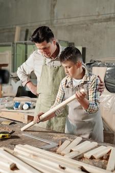 Опытный плотник в фартуке поддерживает сына, пока он учится полировать дерево наждачной бумагой в мастерской