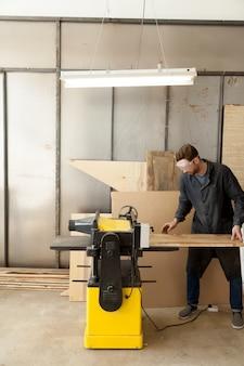 Skilled carpenter working at machine tool