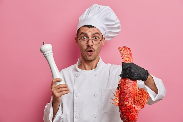 Skilled chef surprised to get very big fish for preparing dish, works as cook in restaurant, holds red sea bass and pepper mill