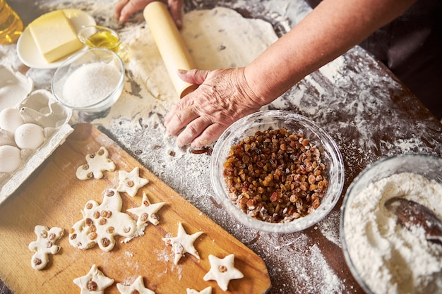 Skilled cook rolling out cookie dough in kitchen