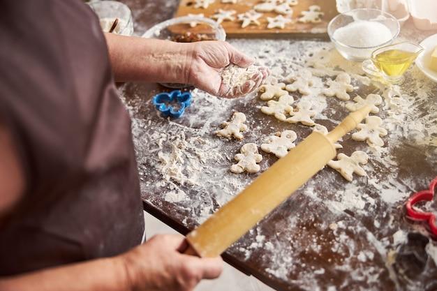 Опытный повар с горстью муки и кухонными принадлежностями