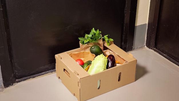 Опытный курьер в джинсовых джинсах ставит коричневый картонный контейнер со свежими овощами на пол возле черной двери крупным планом