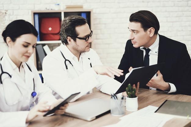Skilled doctor advises businessman in medical office.