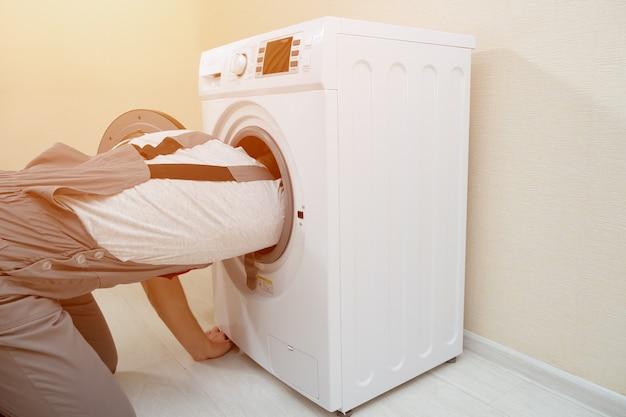 회색 제복을 입은 숙련된 직원이 베이지색 벽 뒷면 보기에서 나무 바닥에 있는 깨진 세탁기를 수리하기 시작합니다.