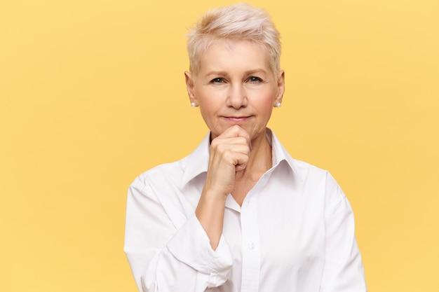 Abile designer femmina matura con esperienza che indossa elegante camicia bianca che tocca il mento, con espressione facciale pensierosa, pensando al concetto di nuovo progetto di interior design. pensieri e idee