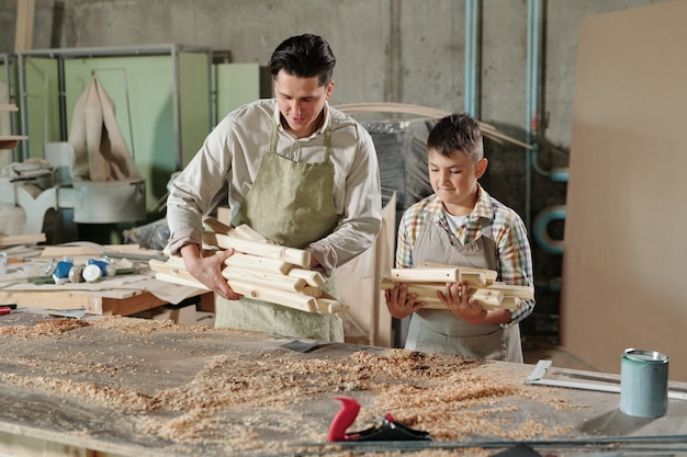 Skilled father in apron putting wooden planks on desk while preparing for woodworking with son in carpentry shop