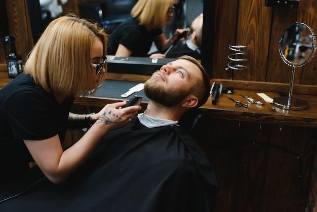 プロのレトロな理髪店でブルネットの大人の男のひげを切る熟練した女性の理髪店。