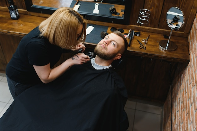 Skilled female barber cutting a beard of brunette adult guy in professional retro barbershop. Premium Photo