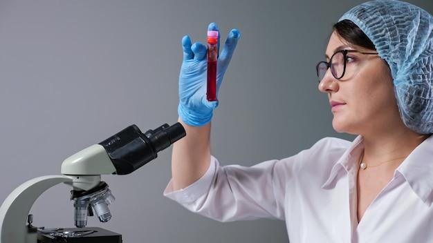 안경을 쓴 숙련된 여성 과학자는 현대 병원에서 일하는 현미경 근처의 시험관에 있는 붉은 액체 샘플을 봅니다.