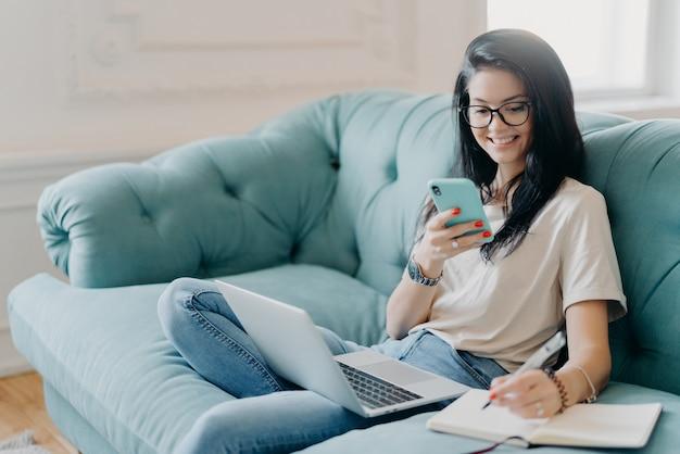 숙련 된 여학생이 프로젝트 발표, 휴대 전화로 필요한 정보 검색, 무릎에 노트북 열기, 캐주얼 옷 입기, 아늑한 방 소파에서 포즈, 온라인 채팅