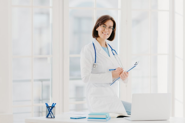 Skilled female therapist or cardiologist writes information at clipboard, ready to consult and cure patients
